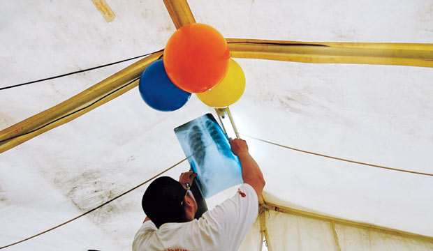 emergency physician holding an X-ray to the sunlight in a tent