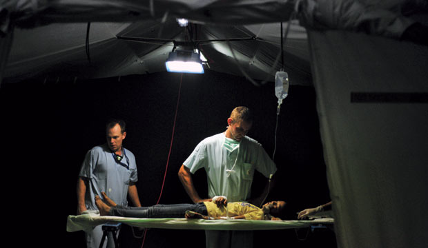 Doctors looking a wounded boy over in a tent